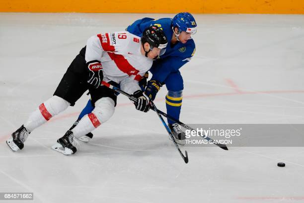 Switzerland's forward Reto Schappi vies with Sweden's forward Victor Rask during the IIHF Men's World Championship quarter final ice hockey match...