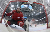 Switzerland's forward Thomas Rufenacht falls into the empty net as he fails to score during a preliminary round group B match between Latvia and...
