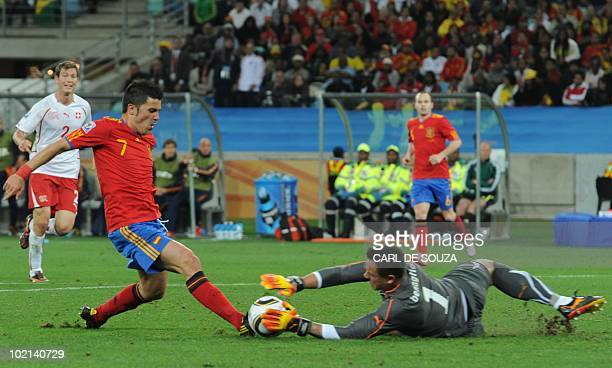 Switzerland's goalkeeper Diego Benaglio leaps for a save as Spain's striker David Villa tries for a chance on goal fights for the ball with during...