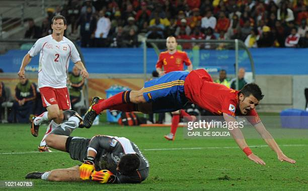 Switzerland's goalkeeper Diego Benaglio saves the ball as Spain's striker David Villa falls to the ground after trying for a chance on goal during...