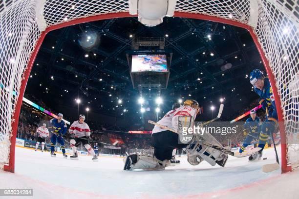 Switzerland's goalkeeper Leonardo Genoni vies with Sweden's forward Joakim Nordstrom during the IIHF Men's World Championship quarter final ice...