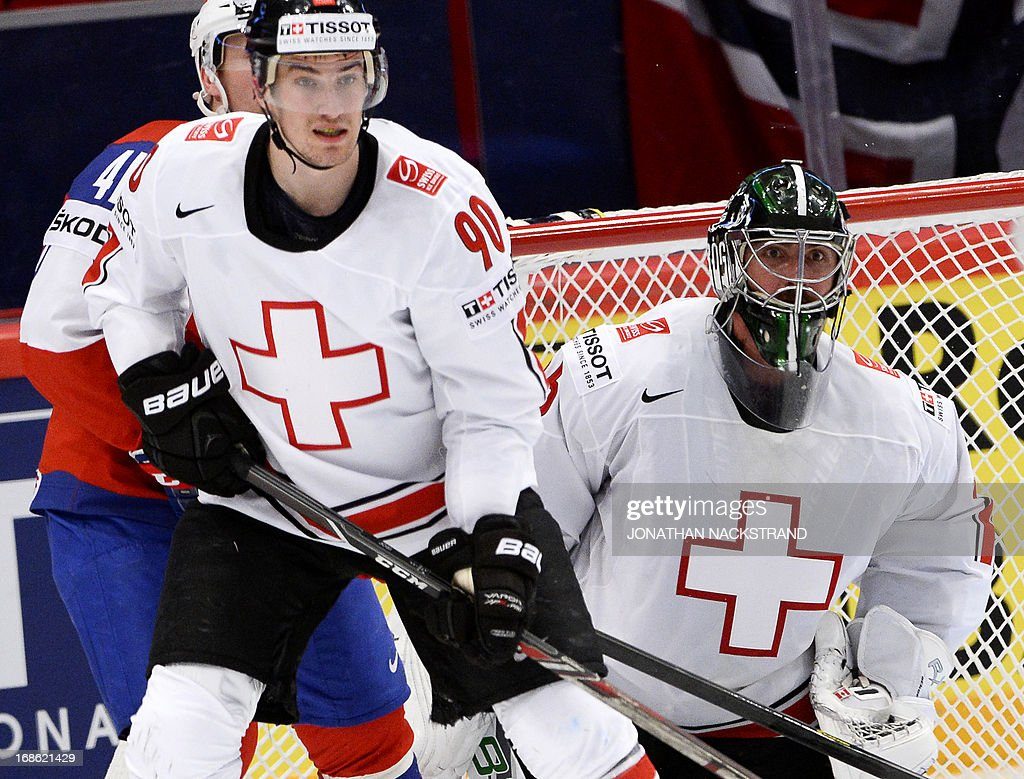 Switzerland's goalkeeper Martin Gerber (R) looks for the puck as his teammate Roman Josi and Norway's Patrick Thoresen (L) vie during the preliminary round match Norway vs Switzerland at the 2013 IIHF Ice Hockey World Championships on May 12, 2013 in Stockholm.