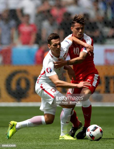 Switzerland's Granit Xhaka and Poland's Arkadiusz Milik battle for the ball