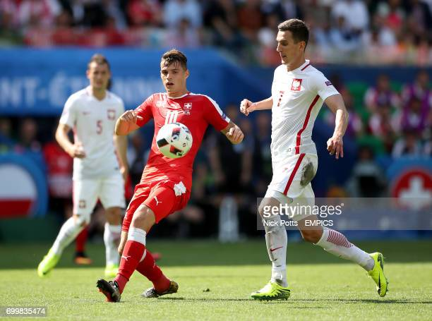 Switzerland's Granit Xhaka and Poland's Arkadiusz Milik