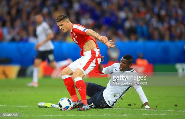 Switzerland's Granit Xhaka shirt rips as he battles for the ball with France's Paul Pogba