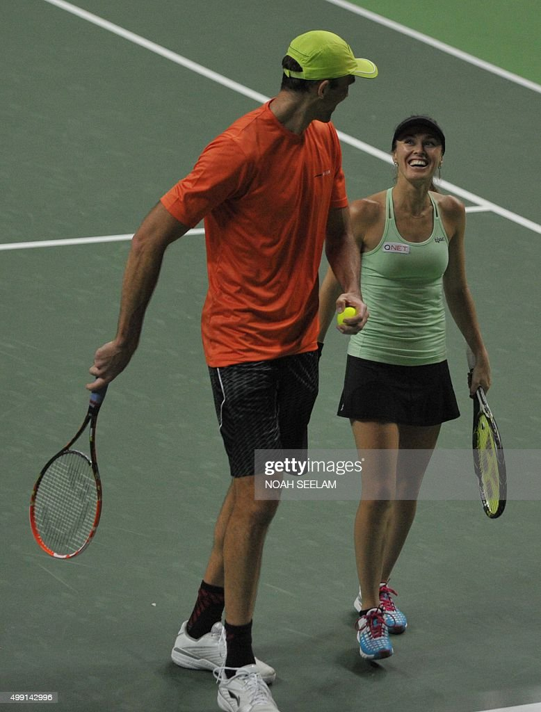 Switzerland's Hyderabad Aces Martina Hingis and partner Croatian Ivo Karlovic celebrate a point during their mixed doubles match against Serbia's...