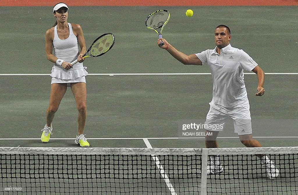 Switzerland's Hyderabad Aces Martina Hingis looks on as partner Russia's Mikhail Youzhny plays a shot during their mixed doubles against Poland's...