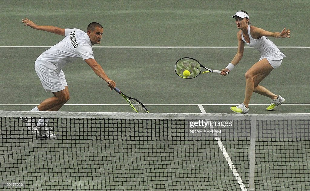 Switzerland's Hyderabad Aces Martina Hingis plays a shot as partner Russia's Mikhail Youzhny looks on during their mixed doubles against Poland's...