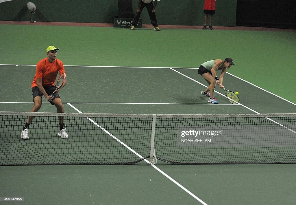 Switzerland's Hyderabad Aces Martina Hingis plays a shot as partner Croatian Ivo Karlovic looks on during a mixed doubles match against Serbia's...
