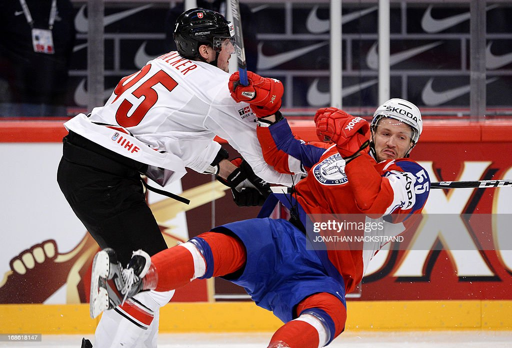 Switzerland's Julian Walker (L) and Norway's Ole-Kristian Tollefsen vie for the puck during the preliminary round match Norway vs Switzerland at the 2013 IIHF Ice Hockey World Championships on May 12, 2013 in Stockholm.
