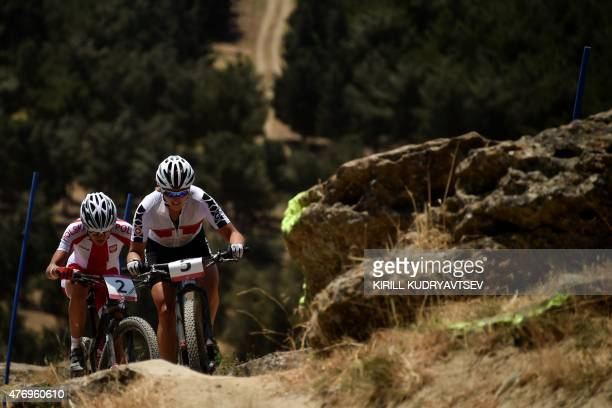 Switzerland's Kathrin Stirnemann and Poland's Maja Wloszczowska compete in the women's cross country mountain bike cycling event of the 2015 European...