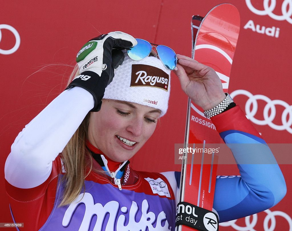 Switzerland's Lara Gut adjusts her sunglasses as she poses on the podium of the FIS Ski World Cup Ladies's Super G, on January 26, 2014 in Cortina d'Ampezzo. Swiss Lara Gut underlined her Olympic super-G title ambitions by claiming her third World Cup win of the season in the discipline at Cortina d'Ampezzo. Liechtenstein's Tina Weirather was second at 0.12secs with Germany's Maria Hoefl-Riesch extending her overall World Cup lead by finishing third at 0.61 to claim her third podium place in four days of racing in the Italian Dolomites.