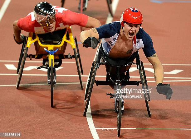 Switzerland's Marcel Hug looks toward Britain's David Weir as he reacts to winning the men's 800m T54 final during the athletics competition at the...