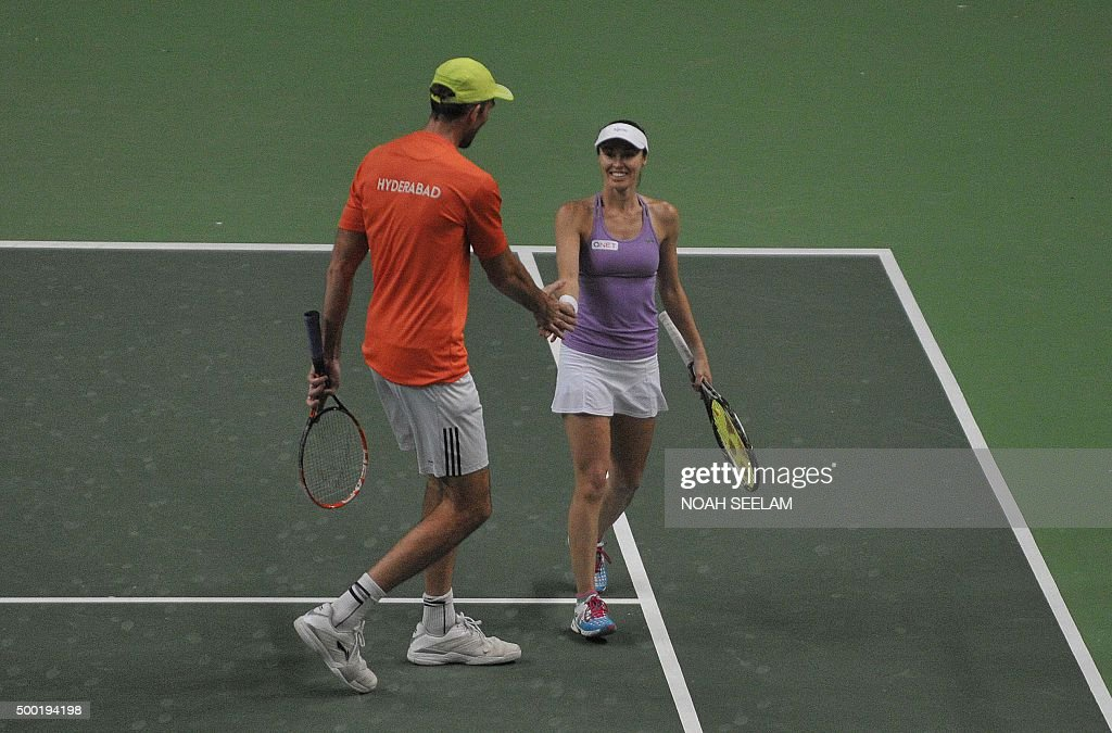 Switzerland's Martina Hingis interacts with partner Croatia's Ivo Karlovic of Hyderabad Aces during a mixed doubles final match against Cypriot...