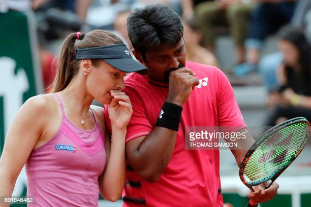 Switzerland's Martina Hingis speaks to India's Leander Paes during their mixed doubles tennis match against Slovenia's Katarina Srebotnik and South...