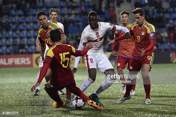 Switzerland's midfielder Denis Zakaria vies with Andorra's players during the FIFA World Cup 2018 football qualifier between Andorra and Switzerland...