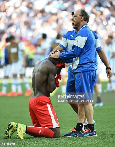 Switzerland's midfielder Gelson Fernandes is comfroted by members of the coaching squad as he reacts after losing their Round of 16 football match...