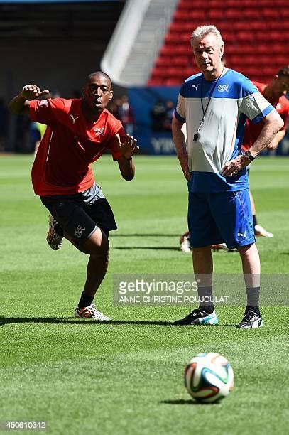 Switzerland's midfielder Gelson Fernandes runs with the ball past coach Ottmar Hitzfeld during a team training session at The Mane Garrincha National...