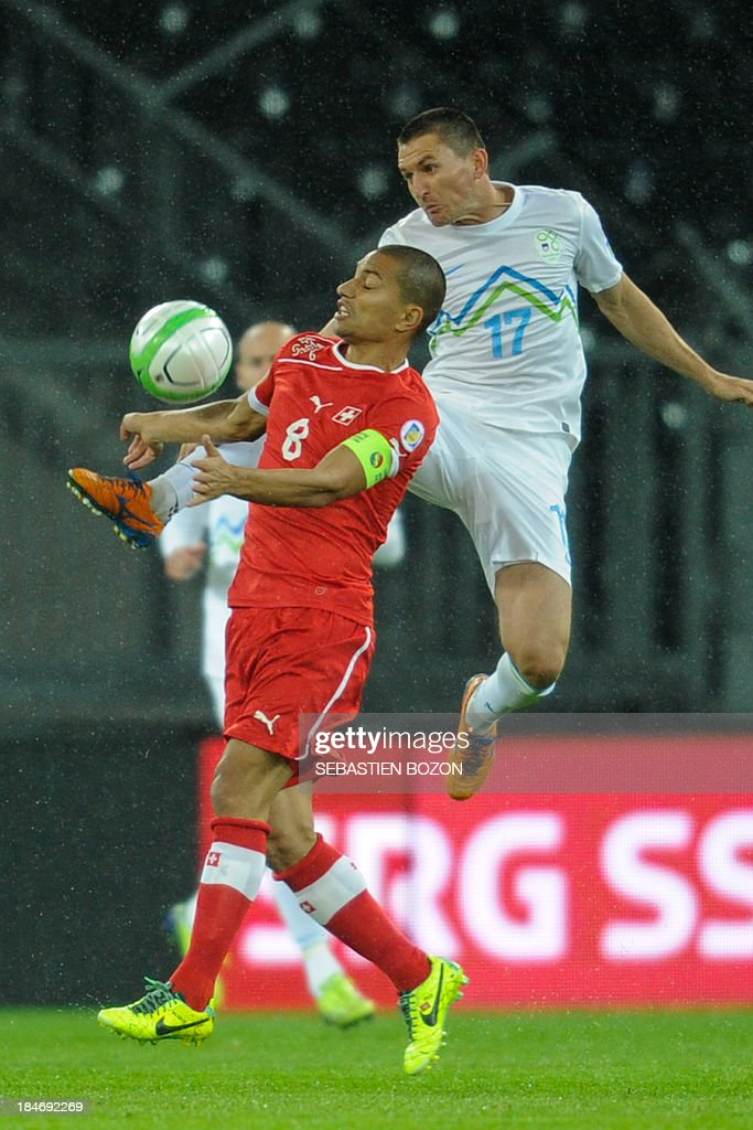 Switzerland's midfielder Goekhan Inler (L) vies with Slovenia's midfielder Andraz Kirm (L) during the world cup 2014 qualifiying football match Switzerland vs Slovenia on October 15, 2013, at the Stade de Suisse, in Bern.