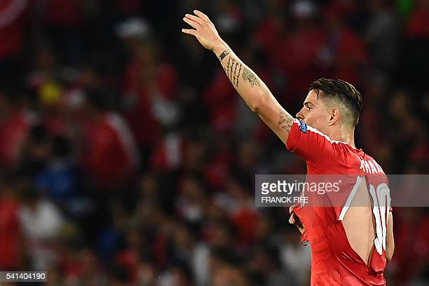 TOPSHOT Switzerland's midfielder Granit Xhaka in a ripped shirt gestures during the Euro 2016 group A football match between Switzerland and France...