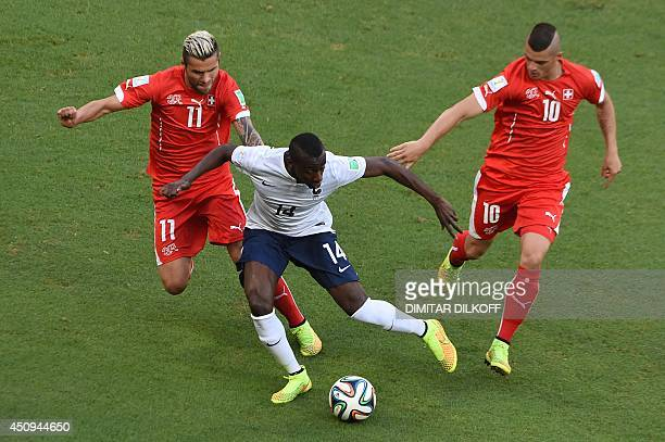 Switzerland's midfielder Valon Behrami and Switzerland's midfielder Granit Xhaka vie with France's midfielder Blaise Matuidi during a Group E...