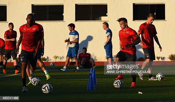 Switzerland's midfielder Xherdan Shaqiri and midfielder Gelson Fernandes exercise during a training session on June 07 2014 at the municipal stadium...