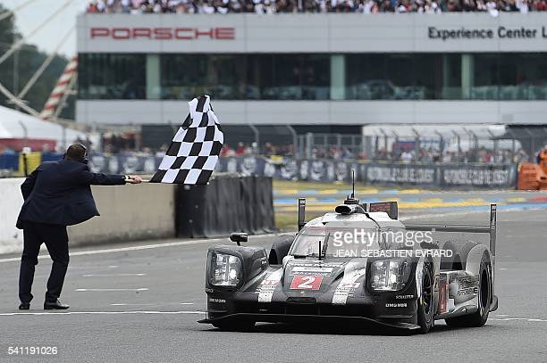 Switzerland's Neel Jani takes the Porsche 919 Hybrid N°2 over the finish line to win the 84th Le Mans 24hours endurance race on June 19 2016 in Le...