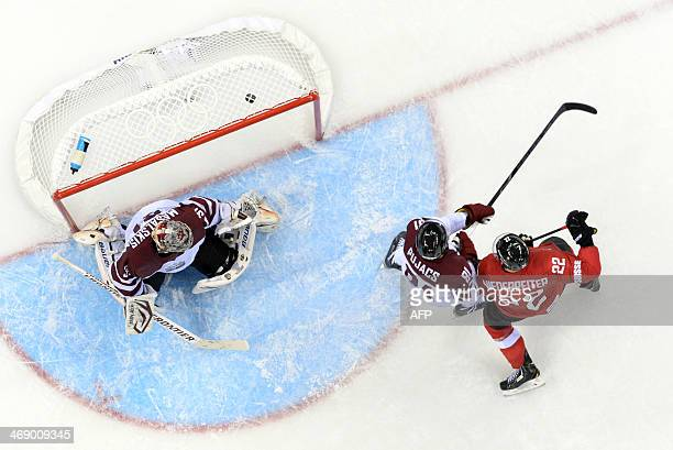 Switzerland's Nino Niederreiter vies with Latvia's Georgijs Pujacs as team mate Switzerland's Simon Moser scores a goal during the Men's Ice Hockey...
