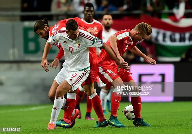 Switzerland's Ricardo Rodríguez Nico Elvedi and Breel Embolo vie with Hungary's Adam Szalai during a WC 2018 football qualification match Hungary v...