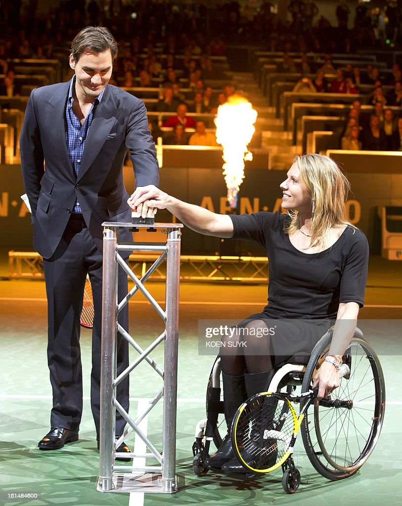 Switzerland's Roger Federer (l) and Dutch wheelchair tennis player Esther Vergeer take part in the opening ceremony of the ABN AMRO tennis Tournament in Rotterdam, on February 11, 2013.