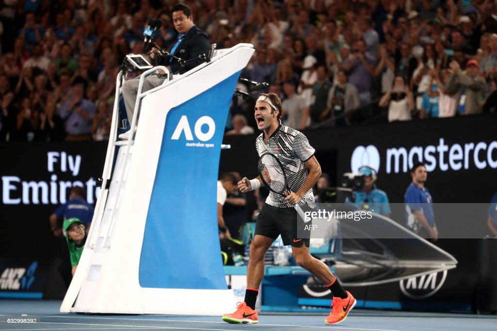 TOPSHOT - Switzerland's Roger Federer celebrates his victory against Spain's Rafael Nadal during the men's singles final on day 14 of the Australian Open tennis tournament in Melbourne on January 29, 2017. / AFP / POOL / Scott BARBOUR / IMAGE