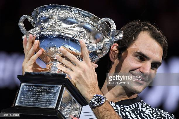 Switzerland's Roger Federer celebrates with the championship trophy during the awards ceremony after his victory against Spain's Rafael Nadal in the...