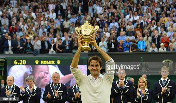 Switzerland's Roger Federer celebrates with the trophy after his men's singles final victory over Britain's Andy Murray on day 13 of the 2012...