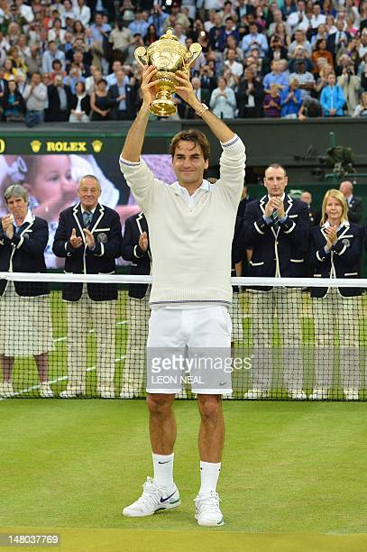 Switzerland's Roger Federer celebrates with the trophy as the officials applaud behind him after his men's singles final victory over Britain's Andy...