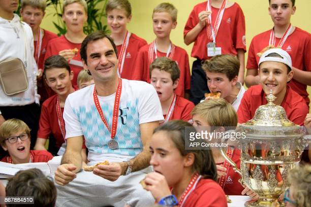 Switzerland's Roger Federer eats pizza with ball kids after defeating Argentina's Juan Martin del Potro in their final match in the Swiss Indoors ATP...