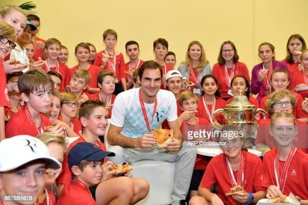 TOPSHOT Switzerland's Roger Federer eats pizza with ball kids after defeating Argentina's Juan Martin del Potro in their final match in the Swiss...