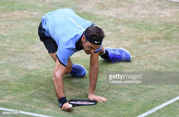 Switzerland's Roger Federer falls during his match against Germany's Mischa Zverev during the ATP tennis tournament in Halle western Germany on June...