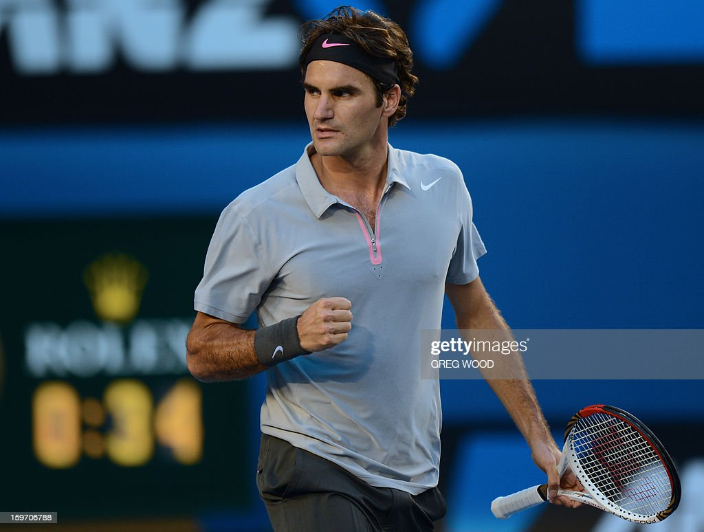 Switzerland's Roger Federer gestures as he celebrates winning the first set during his men's singles match against Australia's Bernard Tomic on the sixth day of the Australian Open tennis tournament in Melbourne on January 19, 2013.