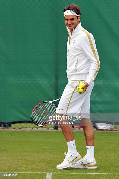 Switzerland's Roger Federer holds tennis balls during a practice session ahead of the 2009 Wimbledon tennis championships which get underway at the...