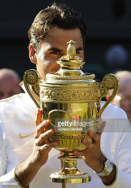 Switzerland's Roger Federer holds the trophy after winning against US Andy Roddick in the men's final match on Day 13 at the 2009 Wimbledon tennis...