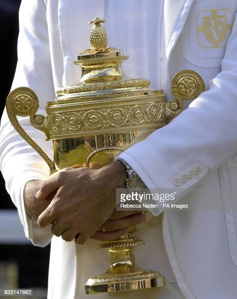Switzerland's Roger Federer holds the trophy after winning the Men's Final against Spain's Rafael Nadal during The All England Lawn Tennis...