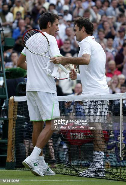 Switzerland's Roger Federer is consoled by winner Ukraine's Sergiy Stakhovsky during day Three of the Wimbledon Championships at The All England Lawn...