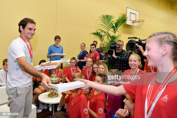 Switzerland's Roger Federer offers pizza to ball kids after defeating Argentina's Juan Martin del Potro in their final match in the Swiss Indoors ATP...