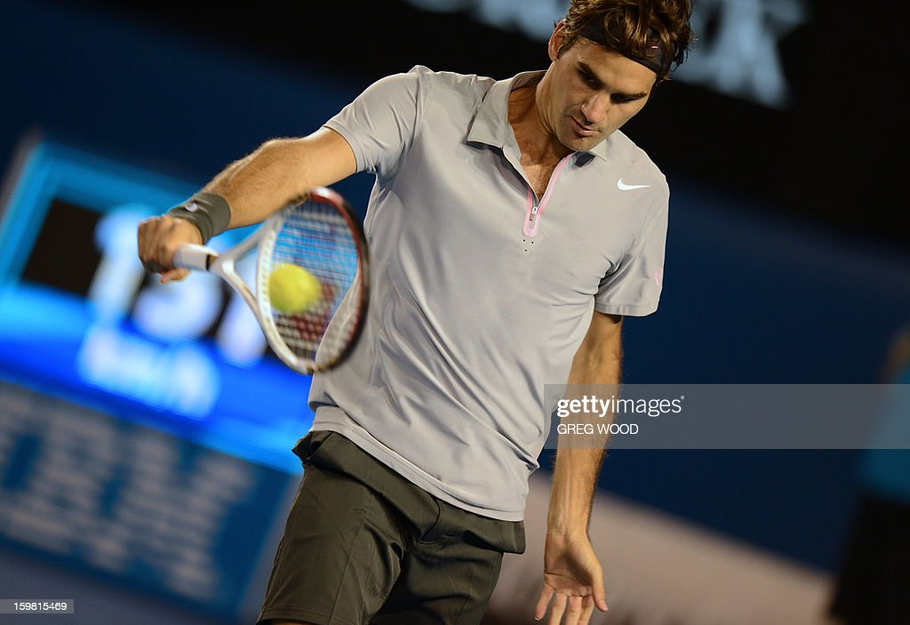 Switzerland's Roger Federer plays a return during his men's singles match against Canada's Milos Raonic on the eighth day of the Australian Open tennis tournament in Melbourne on January 21, 2013. AFP PHOTO/ GREG WOOD IMAGE STRICTLY RESTRICTED TO EDITORIAL USE - STRICTLY NO COMMERCIAL USE