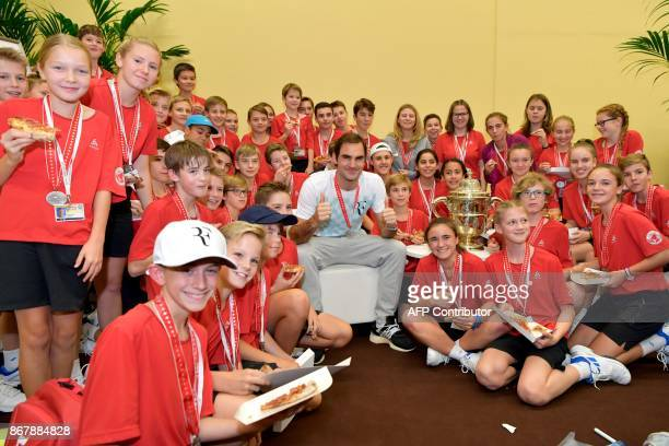 Switzerland's Roger Federer poses with ball kids after defeating Argentina's Juan Martin del Potro in their final match in the Swiss Indoors ATP 500...