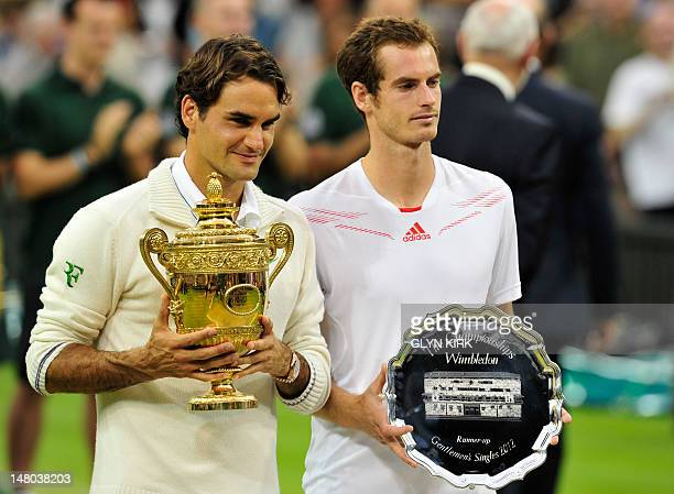 Switzerland's Roger Federer poses with the trophy with runnerup Britain's Andy Murray after his men's singles final victory on day 13 of the 2012...