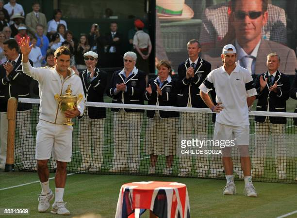 Switzerland's Roger Federer poses with the Wimbledon Trophy after beating Andy Roddick of the US as a television shows an image of former US tennis...