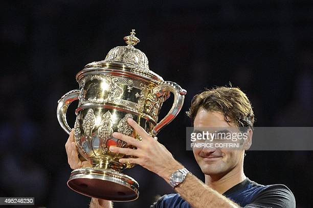 Switzerland's Roger Federer raises his trophy as he celebrates his victory against Spain's Rafael Nadal after their final match at the Swiss Indoors...