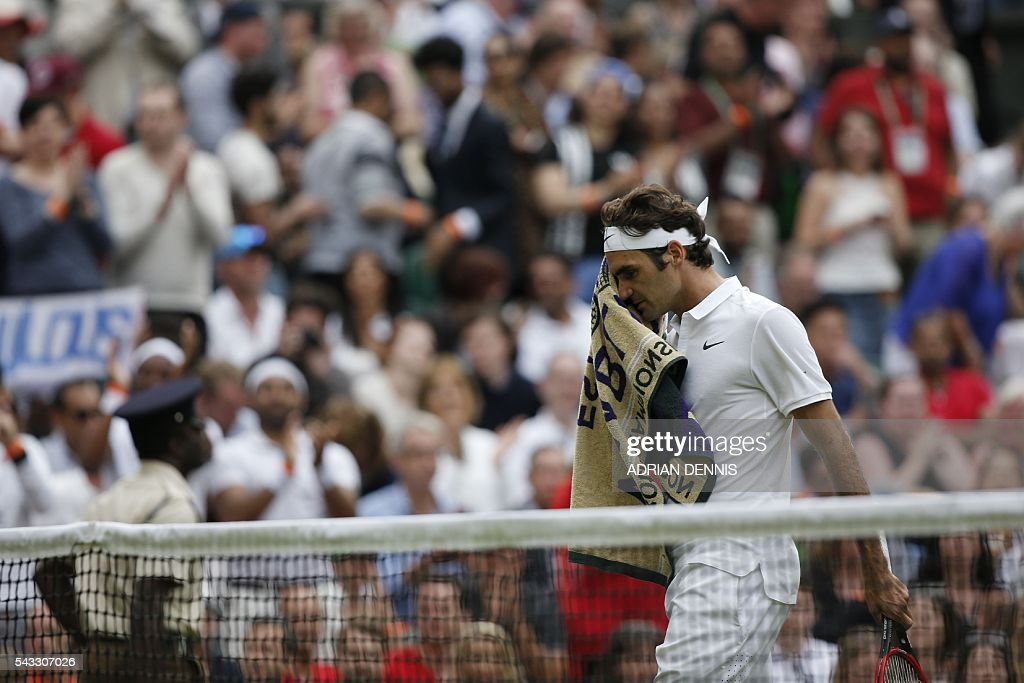 Switzerland's Roger Federer returns to his seat in the break between games against Argentina's Guido Pella during their men's singles first round match on the first day of the 2016 Wimbledon Championships at The All England Lawn Tennis Club in Wimbledon, southwest London, on June 27, 2016. / AFP / ADRIAN