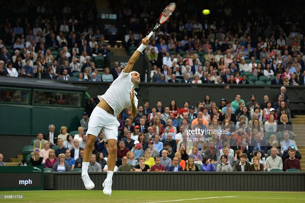 Switzerland's Roger Federer serves against Britain's Marcus Willis in their men's singles second round match on the third day of the 2016 Wimbledon Championships at The All England Lawn Tennis Club in Wimbledon, southwest London, on June 29, 2016. / AFP / GLYN